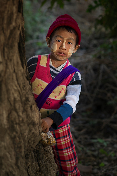 A little boy from a small village on his way to school, wearing the traditional thanaka on his face and carrying his lunch.   Myanmar, 2017.