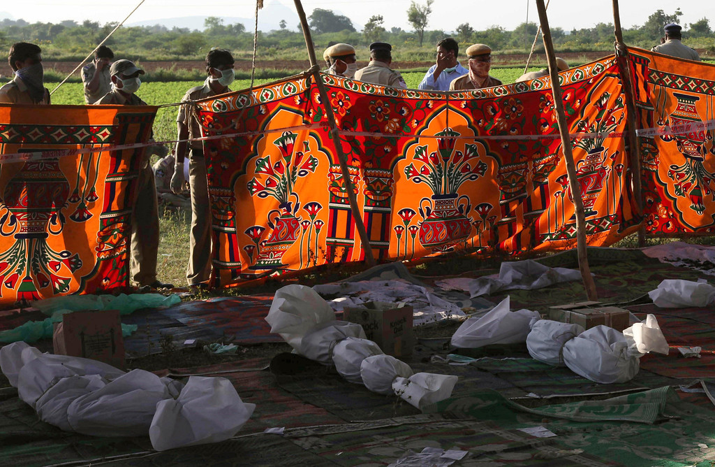 . Indian policemen and others stand near bodies of victims killed in a bus accident at Mehabubnagar, in the southern Indian state of Andhra Pradesh, Wednesday, Oct. 30, 2013.   (AP Photo/Mahesh Kumar A.)