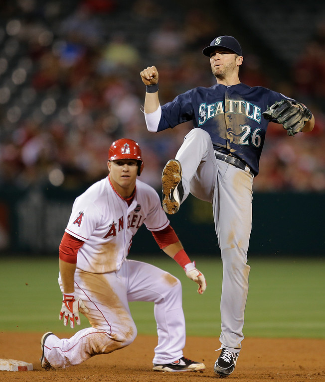 . Seattle Mariners shortstop Brendan Ryan, right, watches his throw go to first base after forcing out Los Angeles Angels\' Mike Trout, left, during the fifth inning of a baseball game in Anaheim, Calif., Tuesday, June 18, 2013. Los Angeles Angels\' Josh Hamilton was out at first. (AP Photo/Jae C. Hong)