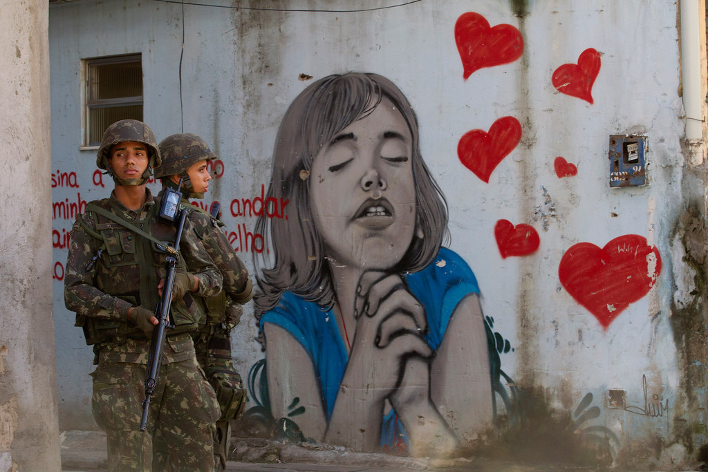 . Army soldiers stand next to a graffiti during an operation to occupy the Mare slum complex in Rio de Janeiro, Brazil, Saturday, April 5, 2014. More than 2,000 Brazilian Army soldiers moved into the Mare slum complex early Saturday in a bid to improve security and drive out the heavily armed drug gangs that have ruled the sprawling slum for decades. (AP Photo/Silvia Izquierdo)