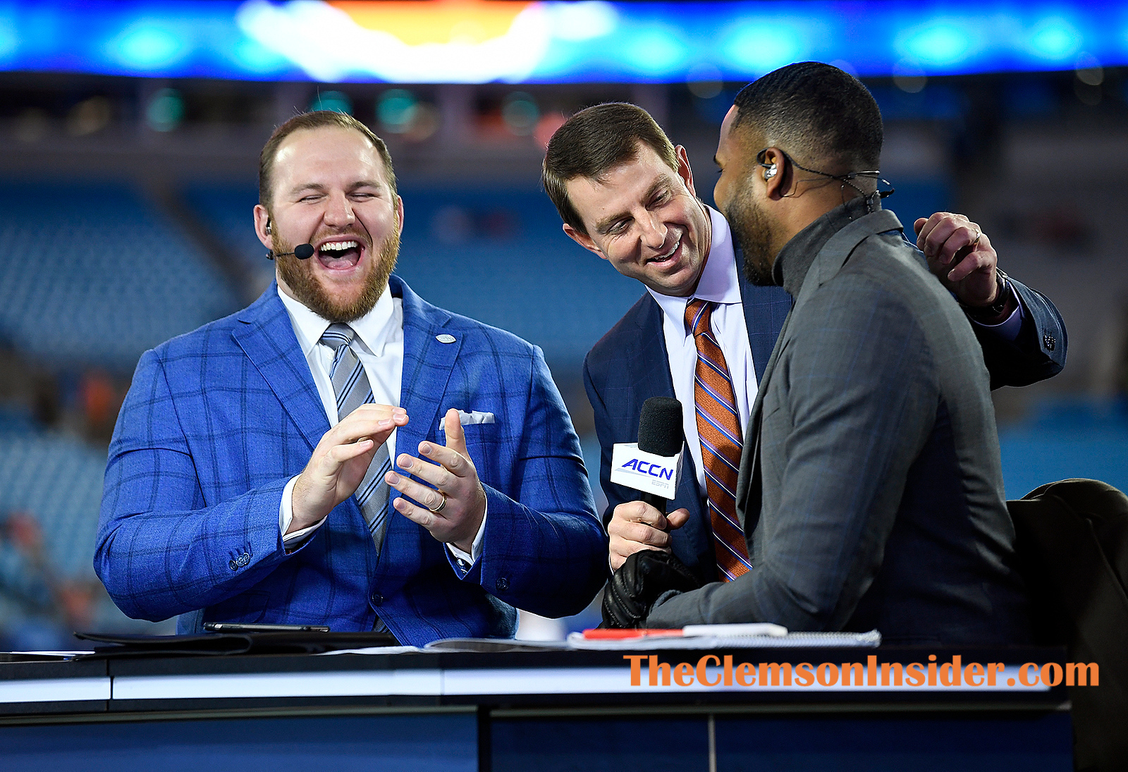Clemson head coach Dabo Swinney surprises Eric Mac Lain and EJ Manuel after crashing the ACC Network field broadcast after he arrived at Bank of America Stadium in Charlotte Saturday, December 7, 2019. Bart Boatwright/The Clemson Insider