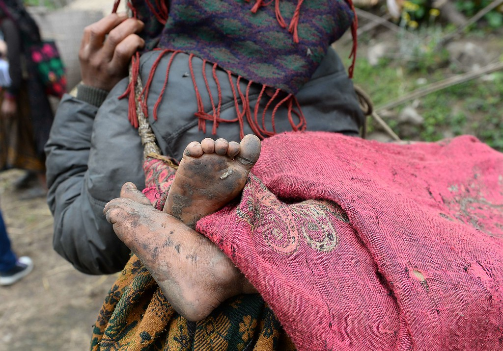 . A mother carries helps carry her son as she arrives to receive relief aid from an Indian Army helicopter at Uiya village, in northern-central Gorkha district on April 29, 2015.   Hungry and desperate villagers rushed towards relief helicopters in remote areas of Nepal, begging to be airlifted to safety, four days after a monster earthquake killed more than 5,000 people.    AFP PHOTO / SAJJAD HUSSAIN/AFP/Getty Images