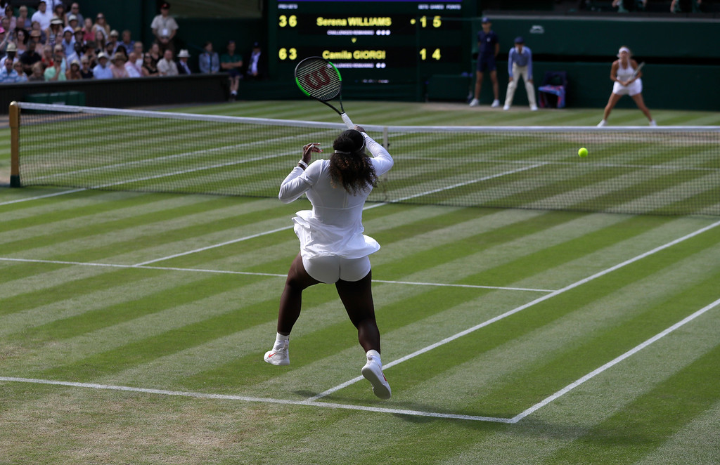 . Serena Williams of the United States returns the ball to Italy\'s Camila Giorgi during their women\'s singles quarterfinals match at the Wimbledon Tennis Championships, in London, Tuesday July 10, 2018. (AP Photo/Kirsty Wigglesworth)