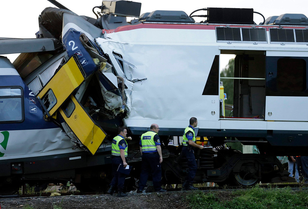 . Police officers are pictured at the site of a head on collision between two trains near Granges-pres-Marnand, near Payerne in western Switzerland, July 29, 2013. The two trains collided at Granges-pr�s-Marnand in the Swiss canton of Vaud on Monday evening, injuring about 40 people, four seriously, Swiss news agency ATS reported. There was no immediate report of any deaths in the crash. REUTERS/Denis Balibouse  (SWITZERLAND - Tags: DISASTER TRANSPORT)