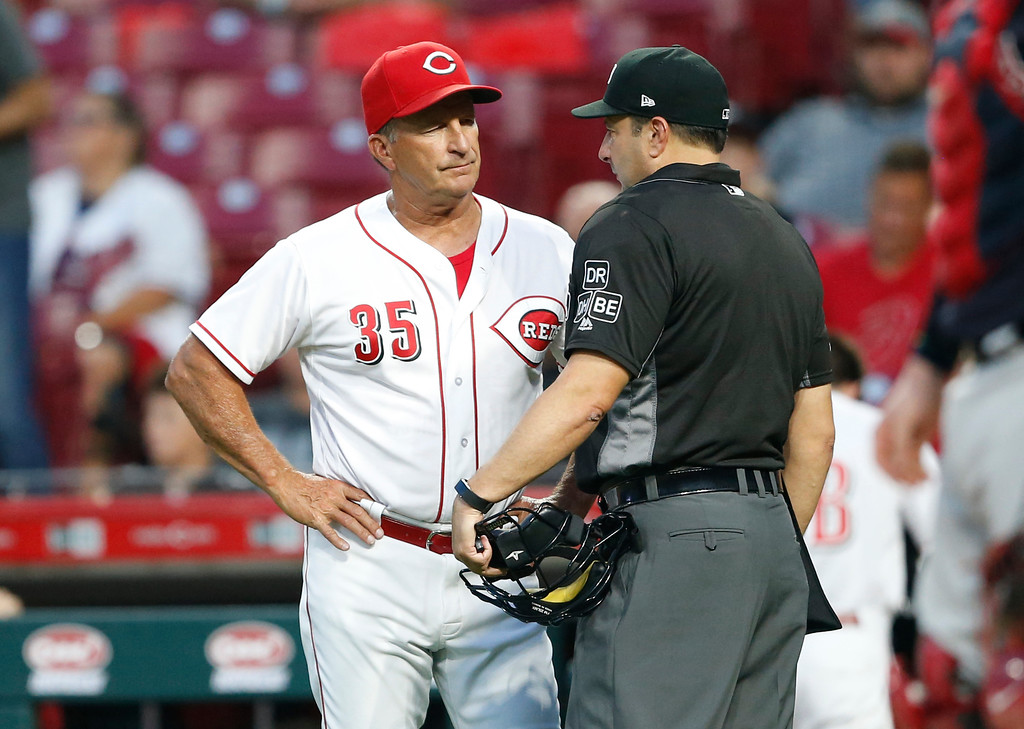 . Cincinnati Reds interim manager Jim Riggleman (35) has a few words with home plate umpire Jim Reynolds over a called third strike on Reds\' Eugenio Suarez during the third inning of a baseball game against the Cleveland Indians, Wednesday, Aug. 15, 2018, in Cincinnati. (AP Photo/Gary Landers)
