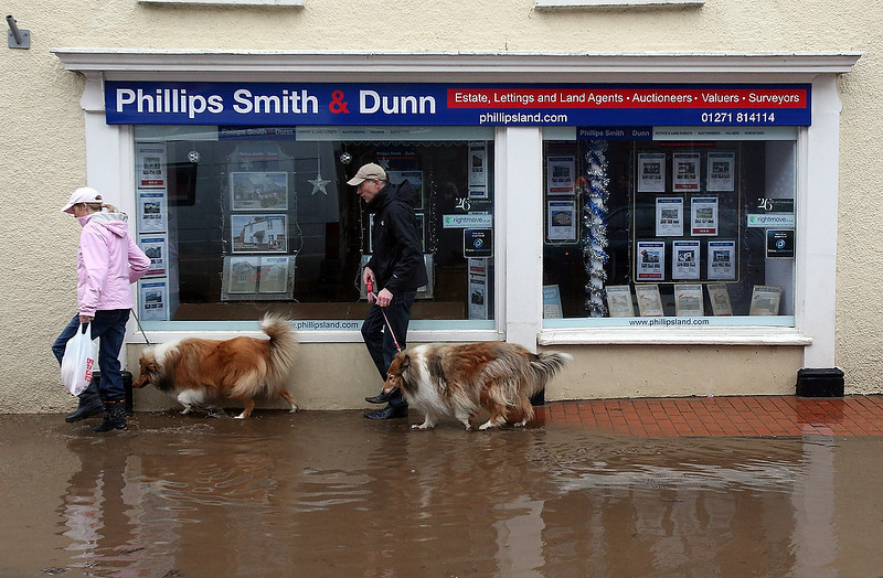 . A couple walking their dogs passes receding flood water in the centre of the Devonshire town of Braunton that was flooded yesterday on December 23, 2012 near Barnstaple, England. Flooding has brought further disruption to many parts of the UK including the South West of England that was particularly badly hit.  The Met Office are warning of further bands of heavy rain tonight and the Environment Agency has issued 100s of flood warnings for England including one severe warning for Cornwall.  (Photo by Matt Cardy/Getty Images)