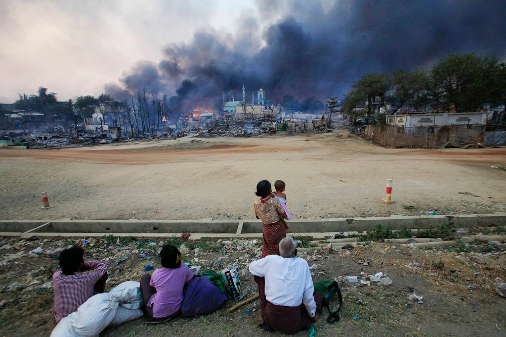 . Smoke rises as people look on in Meikhtila on March 21, 2013. Ethnic hatred has been unleashed in Myanmar since 49 years of military rule ended in March 2011. And it is spreading, threatening the country\'s historic democratic transition. Signs have emerged of ethnic cleansing, and of impunity for those inciting it.   REUTERS/Soe Zeya Tun
