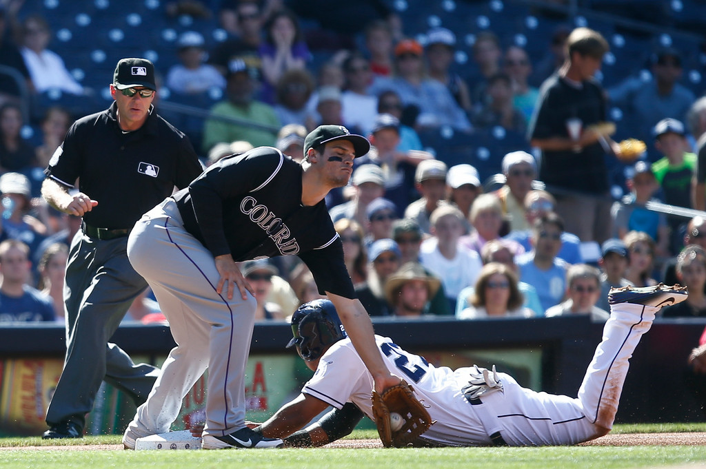 . San Diego Padres\' Yangervis Solarte is safe at third as Colorado Rockies third baseman Nolan Arenado applies a late tag  in the first inning of a baseball game Wednesday, Aug. 13, 2014, in San Diego. Solarte was advancing from first on a single by Jedd Gyorko and would score moments later on a single by Rene Rivera.  (AP Photo/Lenny Ignelzi)