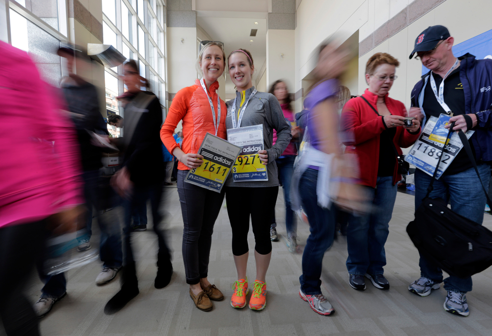 . Cousins Laura Snebold, left, of Washington, and Christine Kenney, of Dedham, Mass., display their bibs to run in Monday\'s 118th Boston Marathon after picking them up Saturday, April 19, 2014, in Boston. (AP Photo/Robert F. Bukaty)