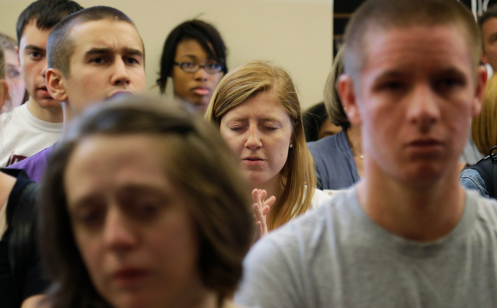 . People bow their heads at a prayer service at the First Free Methodist Church Thursday, June 5, 2014 at Seattle Pacific University in Seattle, where a shooting took place Thursday afternoon.(AP Photo/Ted S. Warren)