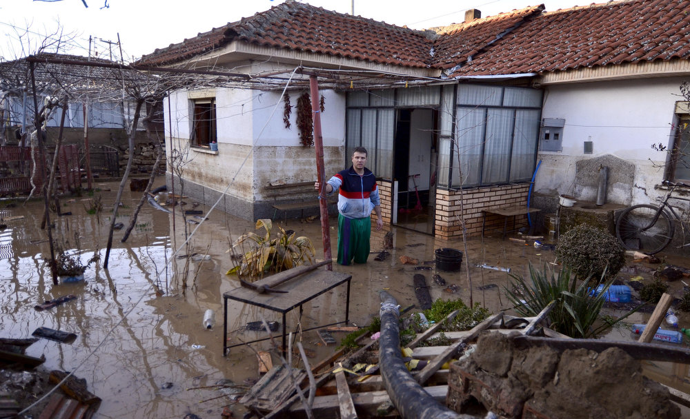 Description of . A man stands knee deep in water,  in the yard of his flooded house in Sveti Nikole, central Macedonia, on Tuesday, Feb. 26, 2013.  Extensive flooding has hit Macedonia after three days of heavy rain, leaving one man dead, bridges wiped out and homes and fields inundated Tuesday. Police said a 51-year-old man drowned in the northern town of Kumanovo after being swept away Monday while trying to cross a river. His body was discovered Tuesday by rescue crews in the mountainous Balkan nation. (AP Photo/Boris Grdanoski)