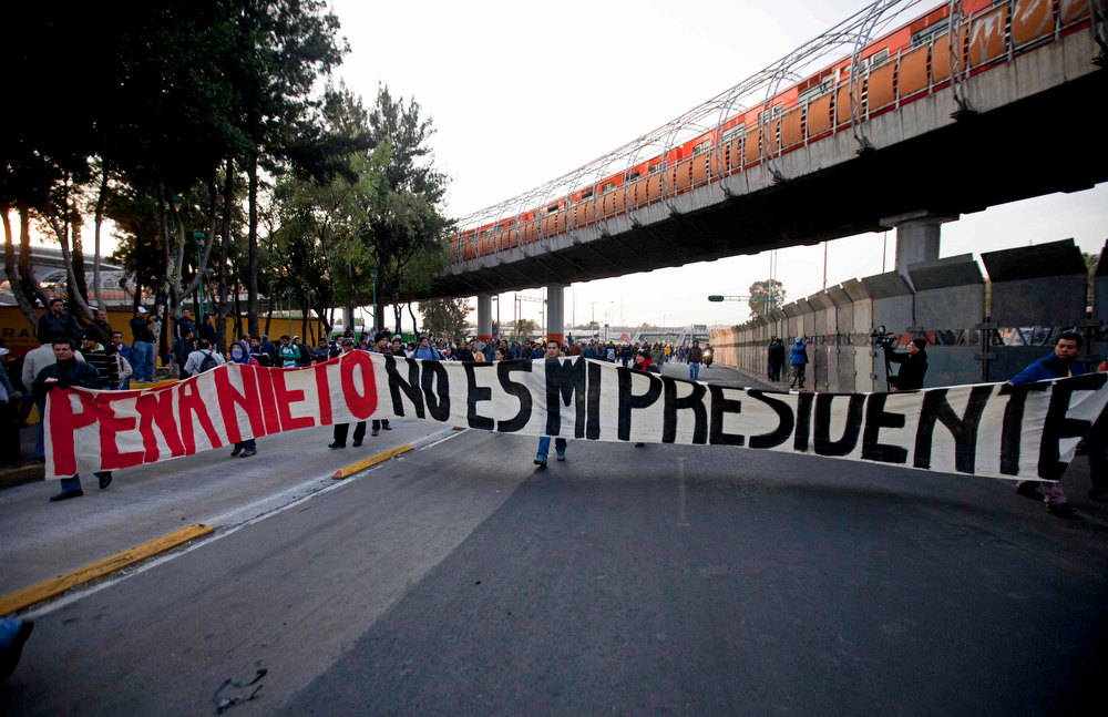 """. Demonstrators hold a banner that reads in Spanish \"""" Pena Nieto is not my president \""""  outside the security steel barrier around the National Congress, where the swearing in of new Mexican President Enrique Pena Nieto is taking place in Mexico City, Saturday Dec. 1, 2012.  Pena Nieto took power at midnight in a symbolic ceremony and will formally take the oath of office Saturday morning after campaigning as the face of a new PRI, a party that claims to be repentant and reconstructed after voted out of the presidency in 2000. (AP Photo/Eduardo Verdugo)"""