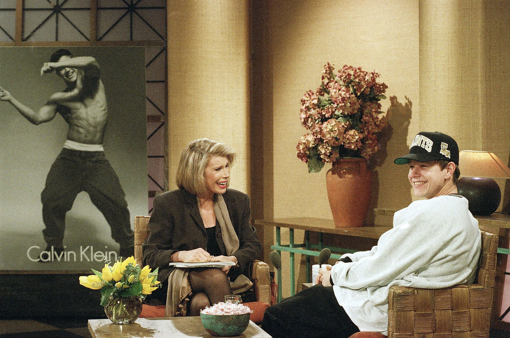 """. Rap star Marky Mark, right, reacts to a joke during his appearance on the \""""Joan Rivers Show\"""" in New York  Wednesday, Dec. 2, 1992. Mark unveiled one of the Calvin Klein underwear ads, background, that feature him wearing little but the product. (AP Photo/Bebeto Matthews)"""