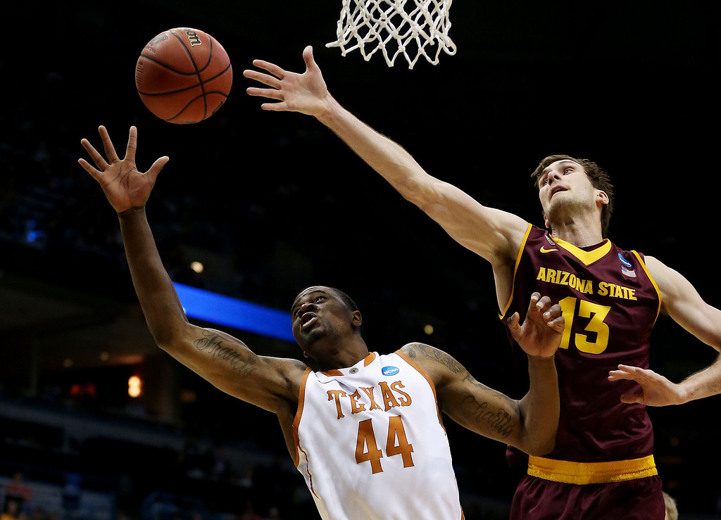 . Prince Ibeh #44 of the Texas Longhorns and Jordan Bachynski #13 of the Arizona State Sun Devils vie for a rebound in the first half during the second round of the 2014 NCAA Men\'s Basketball Tournament at BMO Harris Bradley Center on March 20, 2014 in Milwaukee, Wisconsin.  (Photo by Jonathan Daniel/Getty Images)