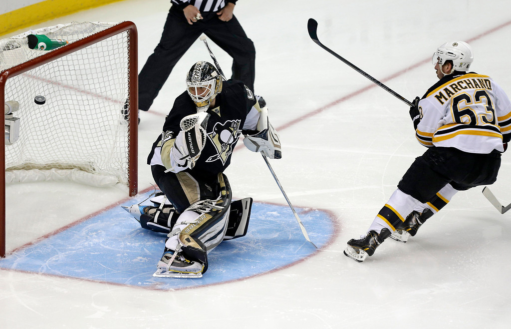 . Boston Bruins\' Brad Marchand (63) puts a shot behind Pittsburgh Penguins goalie Tomas Vokoun (92) for a goal in the first period of Game 2 of the NHL hockey Stanley Cup playoffs Eastern Conference finals, in Pittsburgh on Monday, June 3, 2013. (AP Photo/Gene J. Puskar)