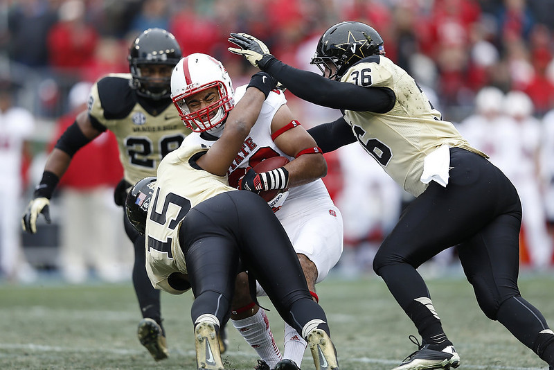 . Archibald Barnes #15 and Chase Garnham #36 of the Vanderbilt Commodores tackle Quintin Payton #88 of the North Carolina State Wolfpack during the Franklin American Mortgage Music City Bowl at LP Field on December 31, 2012 in Nashville, Tennessee. (Photo by Joe Robbins/Getty Images)