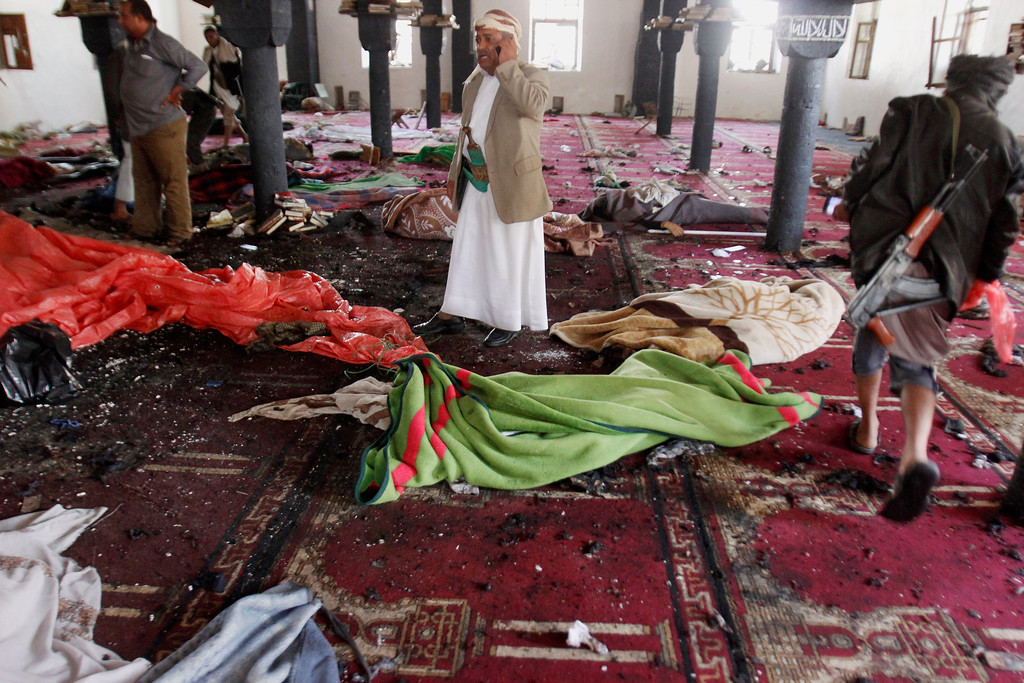 . People stand amid bodies covered with blankets in a mosque after a suicide attack during the noon prayer in Sanaa, Yemen, Friday, March 20, 2015. Triple suicide bombers hit a pair of mosques crowded with worshippers in the capital on Friday, causing heavy casualties, according to witnesses. The attackers targeted mosques frequented by Shiite rebels, who have controlled the capital since September. (AP Photo/Hani Mohammed)