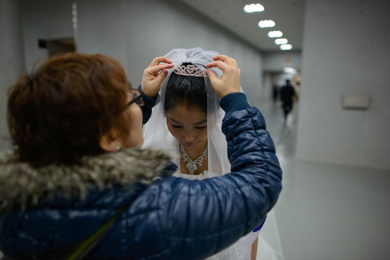 ". A bride prepares for a mass wedding at an event held by the Unification Church in Gapyeong on February 12, 2014. Unification Church members forming 2500 couples from 52 countries were married in a mass wedding in South Korea -- only the second such event since the death of their ""messiah\"" and controversial church founder Sun Myung Moon. (ED JONES/AFP/Getty Images)"