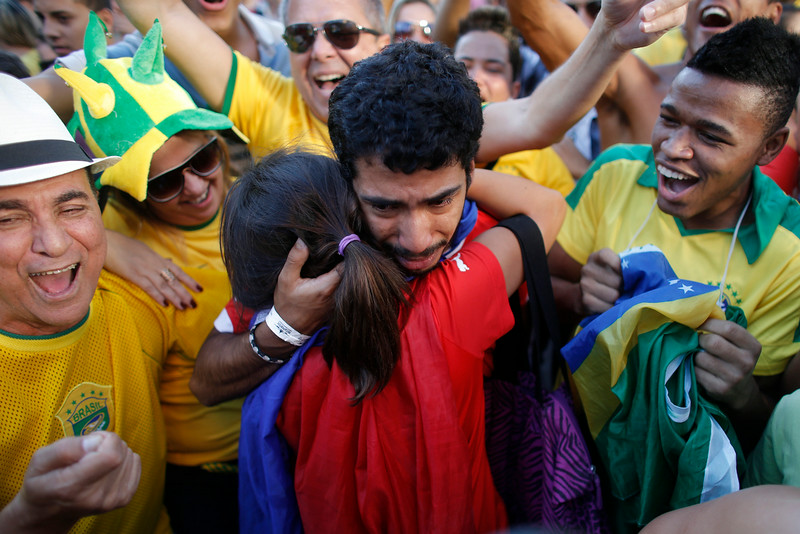 . A Chilean couple hug and cry, center, next to cheering Brazilian fans after Brazil defeated Chile on a World Cup round of 16 soccer match in Belo Horizonte, Brazil, Saturday, June 28, 2014. (AP Photo/Victor R. Caivano)