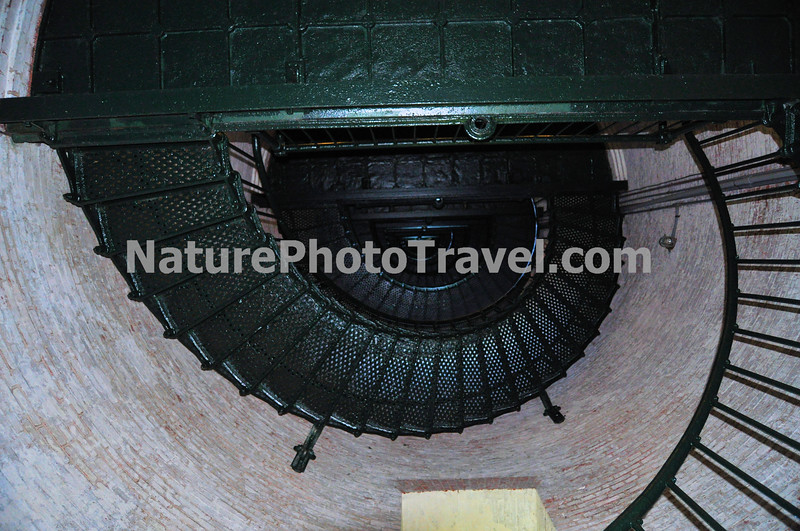 """Currituck Beach Lighthouse (Interior)<br /> On December 1, 1875 the beacon of the Currituck Beach Lighthouse filled the remaining """"dark space"""" on the North Carolina coast between the Cape Henry light to the north and Bodie Island to the south. To distinguish the Currituck Beach Lighthouse from other regional lighthouses, its exterior was left unpainted and gives today's visitor a sense of the multitude of bricks used to form the structure. The lighthouse was automated in 1939 when the United States Coast Guard assumed the duties of the Bureau of Lighthouses. At a height of 158 feet, the night beacon still flashes at 20-second intervals to warn ships hugging the chain of barrier islands along the coast."""
