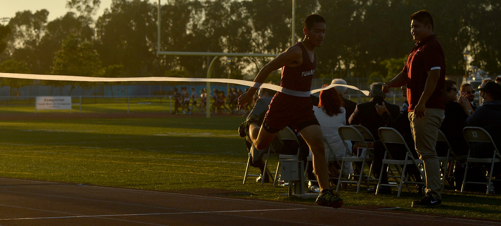 . A runner comes across the finish line as he portrays Louis Zamperini as the Torrance High School Track Team Distance Runners take two laps during the Louis Zamperini Celebration of Life in Torrance CA. Thursday July 31, 2014. (Thomas R. Cordova-Daily Breeze/Press-Telegram)