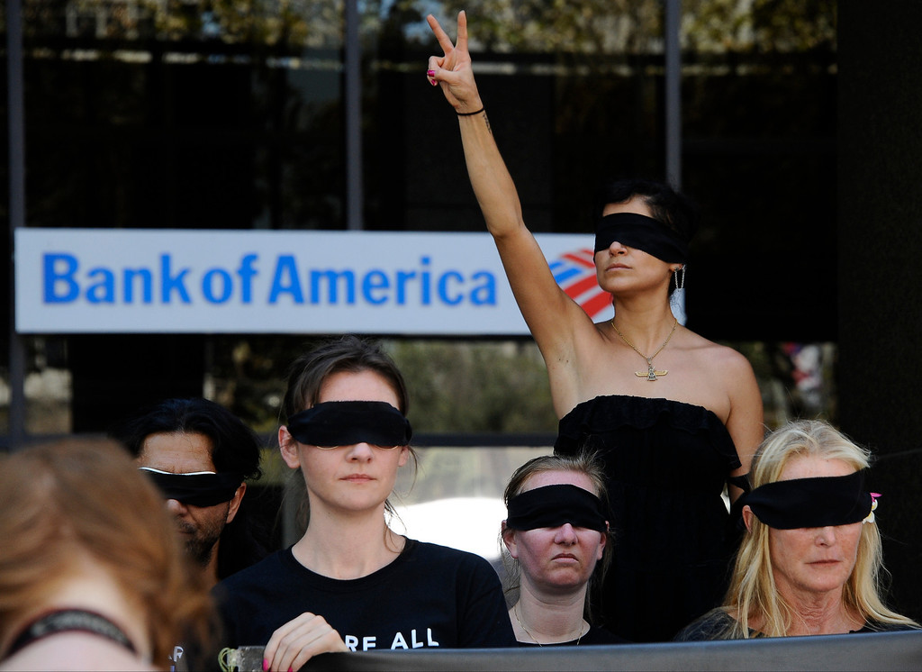 . Marchers stop in front of the Bank of America bank building as they join along with other Southern Californians of human earthlings in more than 14 countries marching this Saturday, August 24 from 12 noon to 3 pm in a global demonstration for total animal liberation. Participants will wear blindfolds to be simultaneously removed as marchers declare, �Our eyes are open to their pain.� Marchers worldwide call on human earthlings to support the right of all planetary citizens/earthlings to live without cruelty or violence regardless of their species and build global solidarity to reduce and ultimately end all forms of animal abuse now normalized in food production, medical and product research, entertainment, clothing and more. The Southern California march starts at Pershing Square at 5th and Hill in downtown Los Angeles; marchers will walk east on 5th to Broadway and then north to Grand Park at 1st and Spring Street at Los Angeles City Hall.  August 24, 2013. Photo by Gene Blevins/LA Daily News