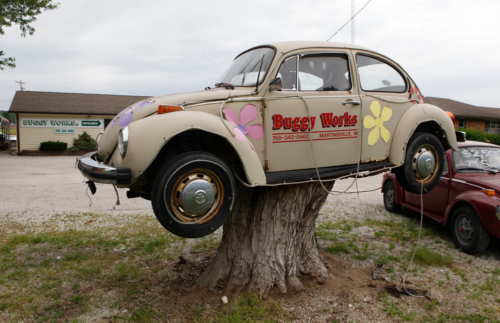 Description of . A VW at Buggy Works sits on a stump in Martinsville, Ind., where it was placed after a 2002 tornado destroyed the tree. (AP Photo/The Herald-Times, Jeremy Hogan)