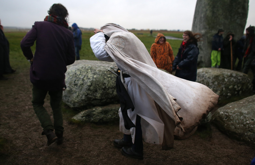 . WILTSHIRE, ENGLAND - DECEMBER 21:  A Druid Merlin holds onto his robes as  walks from the stones as druids, pagans and revellers gather, hoping to see the sun rise as they take part in a winter solstice ceremony at Stonehenge on December 21, 2013 in Wiltshire, England.  (Photo by Matt Cardy/Getty Images)