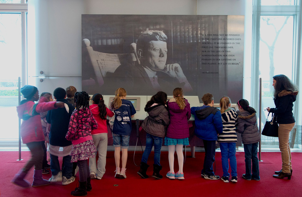""". Children gather around a a multimedia display \""""John F. Kennedy His Life and Legacy\"""" in the grand foyer at the John F. Kennedy Center for the Performing Arts in Washington, Friday, Nov. 22, 2013, on the 50th anniversary of President John F. Kennedy\'s death. (AP Photo/Carolyn Kaster)"""
