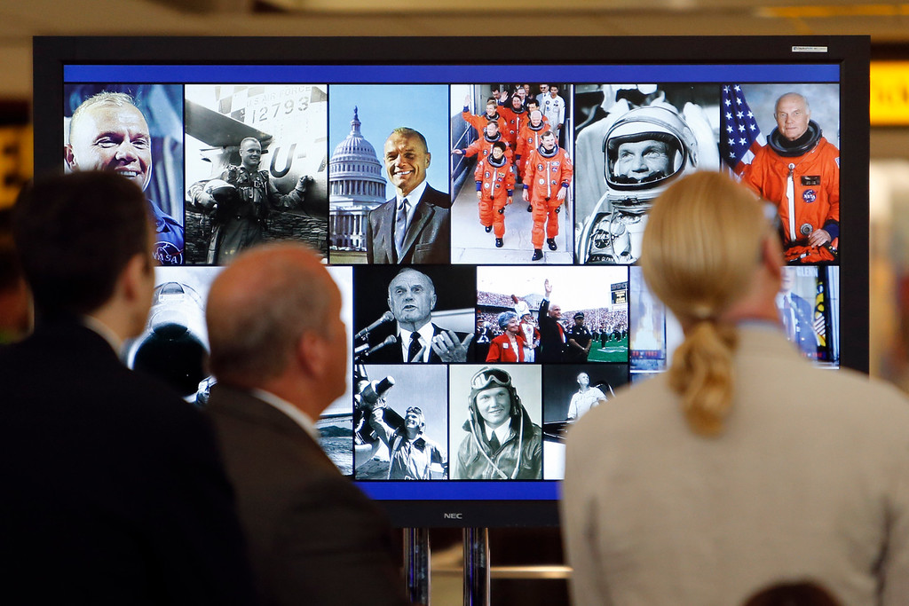 . Visitors watch a video tribute to former U.S. Sen. John Glenn during a celebration for the renaming of Port Columbus International Airport to John Glenn Columbus International Airport Tuesday, June 28, 2016, in Columbus, Ohio. Senate Bill 159, which changes the name of the airport, goes into effect in September. (AP Photo/Jay LaPrete)
