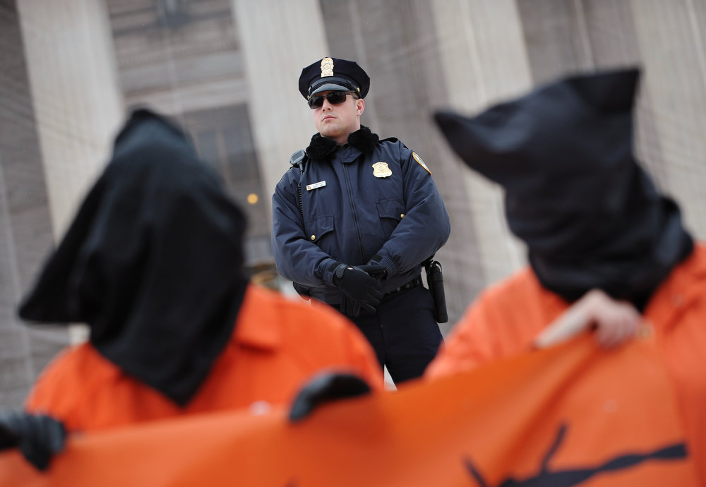 . Police stand guard as hooded demonstrator take part in a rally to call for the closing of the Guantanamo Bay detention center on January 11, 2013 in front of the US Supreme Court on Capitol Hill in Washington. MANDEL NGAN/AFP/Getty Images