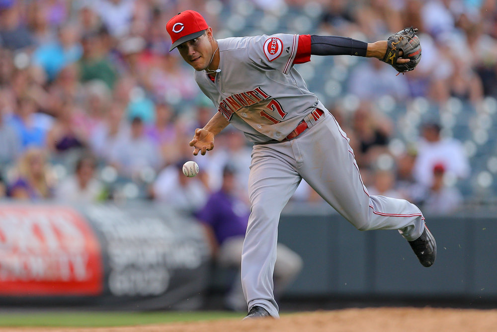 . Third baseman Kris Negron #17 of the Cincinnati Reds is unable to make a play on an infield hit off the bat of Michael Cuddyer (not pictured) of the Colorado Rockies during the seventh inning at Coors Field on August 17, 2014 in Denver, Colorado. The Rockies defeated the Reds 10-9. (Photo by Justin Edmonds/Getty Images)