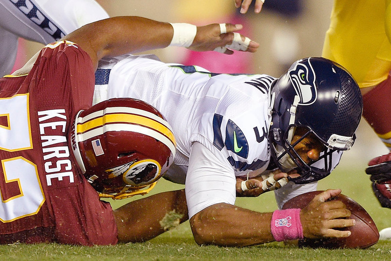. Seattle Seahawks quarterback Russell Wilson (3) recovers his own fumble under pressure from Washington Redskins defensive tackle Frank Kearse (73) during the first half of an NFL football game in Landover, Md., Monday, Oct. 6, 2014. (AP Photo/Nick Wass)