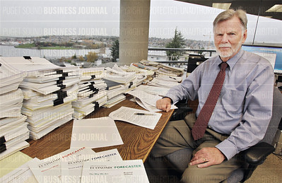 "Economic analyst Richard ""Dick"" Conway, is pictured with his publication, ""The Economic Forecaster"" that he coauthors with colleague Doug Pedersen, as seen in Conway's office in Eastlake overlooking Lake Union in Seattle, Washington"