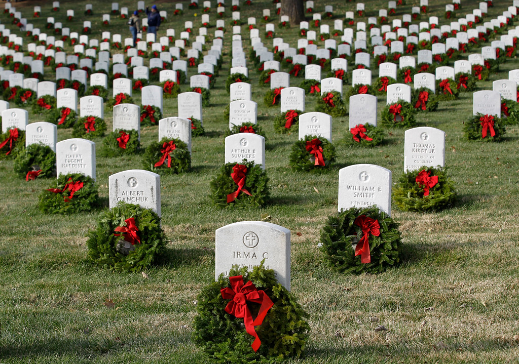 . Holiday wreaths adorn tombstones during Wreaths Across America\'s 150th anniversary, Saturday, Dec. 13, 2014, at Arlington National Cemetery in Arlington, Va. (AP Photo/Luis M. Alvarez)