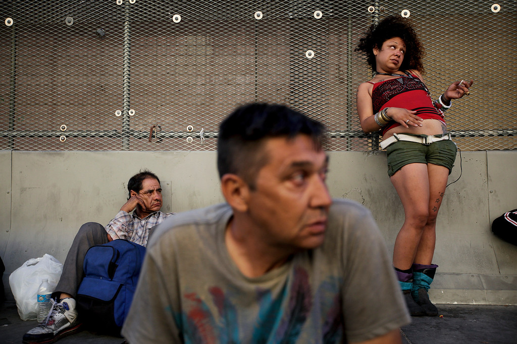 . George Mendez, foreground, a 55-year-old recovering alcoholic, sits in front of a drunk woman in the Skid Row area of Los Angeles on Tuesday, July 23, 2013. The area, originally agricultural until the 1870s when railroads first entered Los Angeles, has maintained a transient nature through the years from the influxes of short-term workers, migrants fleeing economic hardship during the Great Depression, military personnel during World War II and the Vietnam conflict, and low-skilled workers with limited transportation options who need to remain close to the city\'s core, according to the Los Angeles Chamber of Commerce. (AP Photo/Jae C. Hong)