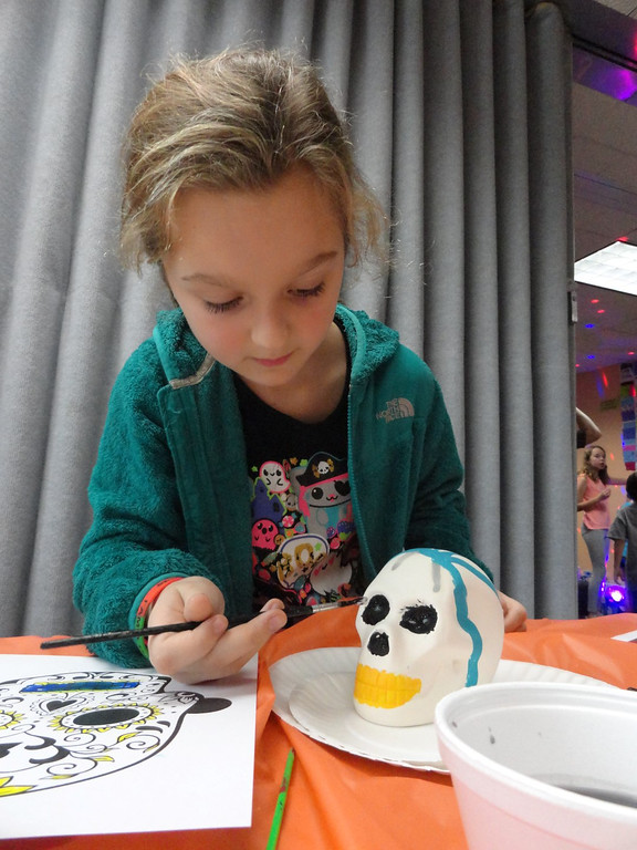 . Lily Mitchell paints large black eyes onto her skeleton�s skull. (Courtesy Mentor Public Library)