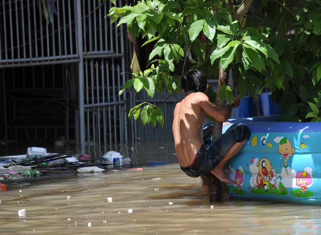 . A young man clinging to a tree in the flood-hit Chaonan district of Shantou, in southern China\'s Guangdong province on on August 19, 2013.  Devastating floods at opposite ends of China have left 105 people dead and another 115 missing in recent days, state media said on August 19.   AFP PHOTOSTR/AFP/Getty Images
