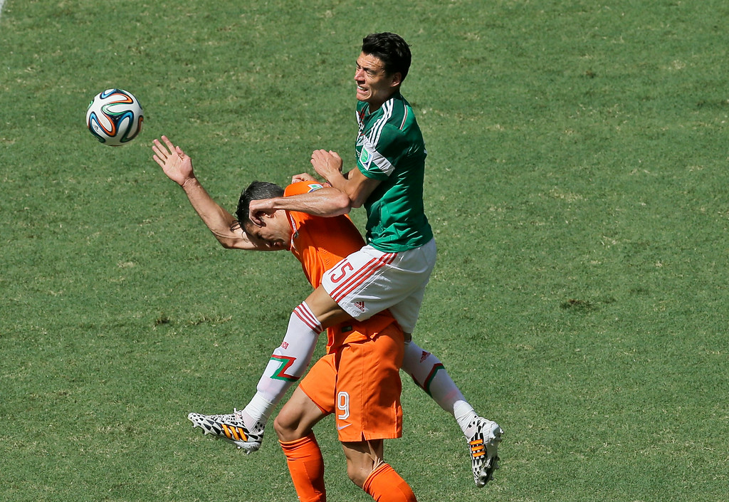. Netherlands\' Robin van Persie, left, and Mexico\'s Hector Moreno challenge for the ball during the World Cup round of 16 soccer match between the Netherlands and Mexico at the Arena Castelao in Fortaleza, Brazil, Sunday, June 29, 2014. (AP Photo/Themba Hadebe)