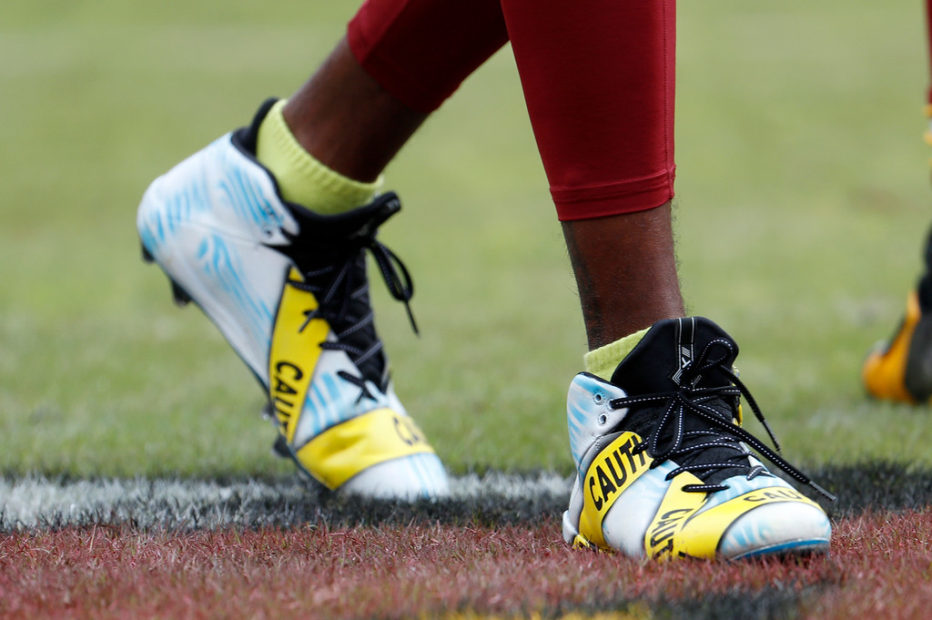. Washington Redskins wide receiver DeSean Jackson (11) wears cleats with a police tape theme during warm ups before an NFL football game against the Cleveland Browns Sunday, Oct. 2, 2016, in Landover, Md. (AP Photo/Carolyn Kaster)