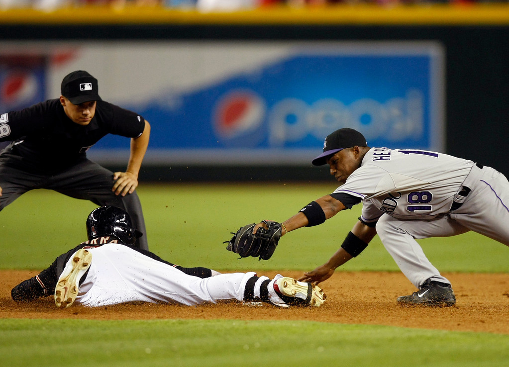 . Arizona Diamondbacks Gerardo Parra (8), left, slides around the tag of Colorado Rockies shortstop Jonathan Herrera (18) in the seventh inning during a baseball game on Saturday, July 6, 2013, in Phoenix. (AP Photo/Rick Scuteri)