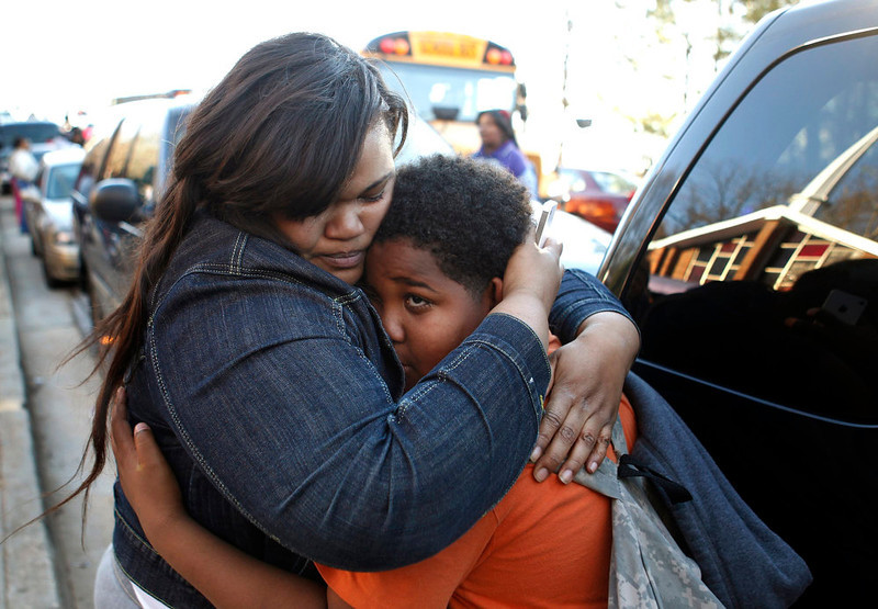 . A mother hugs her son after he was released off a bus near Price Middle School following a shooting at the school in Atlanta, Georgia, January 31, 2013.  One student was shot and another arrested in the latest string of school shootings.  REUTERS/Tami Chappell