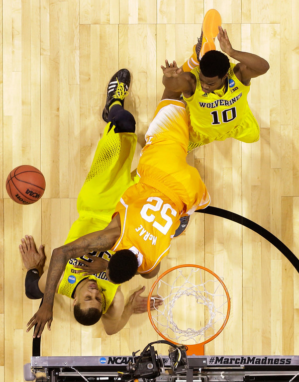 . Michigan\'s Jordan Morgan tries to draw a charge as Tennessee\'s Jordan McRae (52) drives during the second half of an NCAA Midwest Regional semifinal college basketball tournament game Friday, March 28, 2014, in Indianapolis. At right is Michigan guard Derrick Walton Jr. (10). (AP Photo/Michael Conroy)