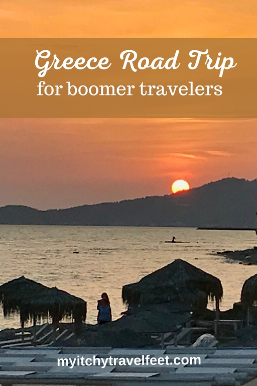 Greece road trip for boomer travelers (text) placed over a photo of a sunset over the water with bungalows in the foreground.