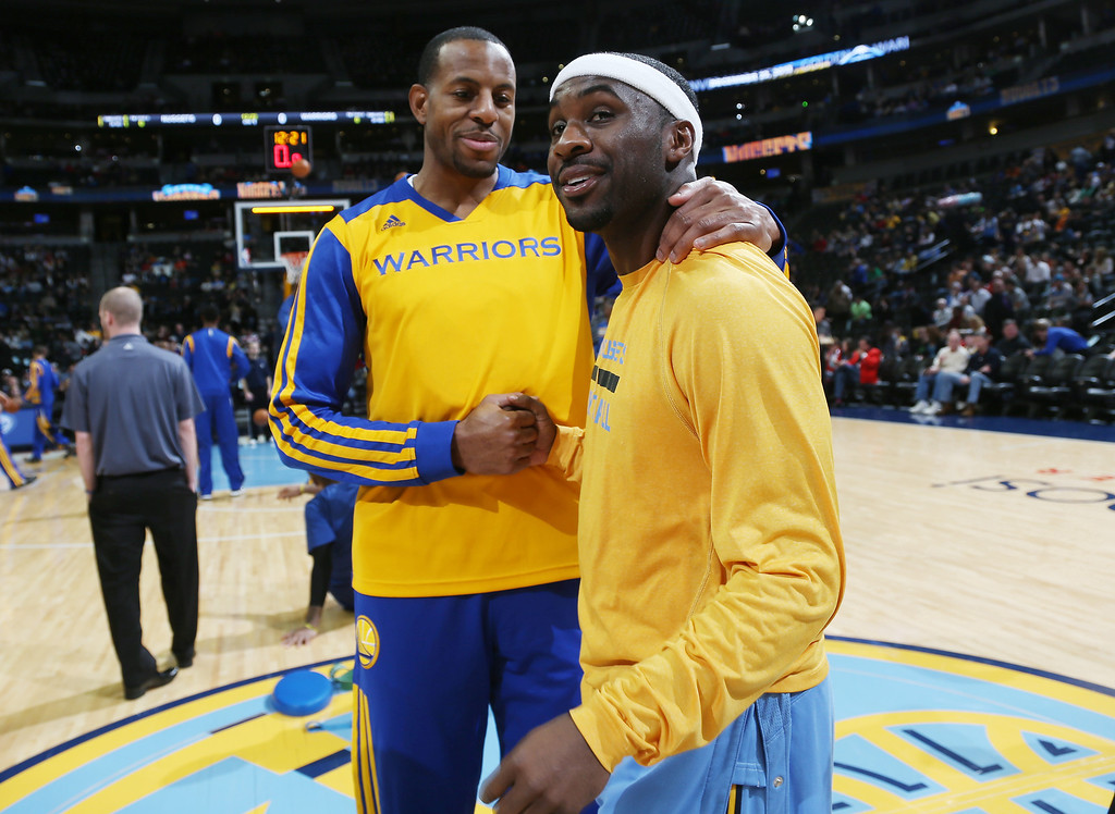 . Golden State Warriors guard Andre Iguodala, left, greets former teammate and Denver Nuggets guard Ty Lawson at center court as the teams warm up for an NBA basketball game in Denver, Monday, Dec. 23, 2013. Iguodala was making his first appearance in Denver since being traded to Golden State in the off-season. (AP Photo/David Zalubowski)
