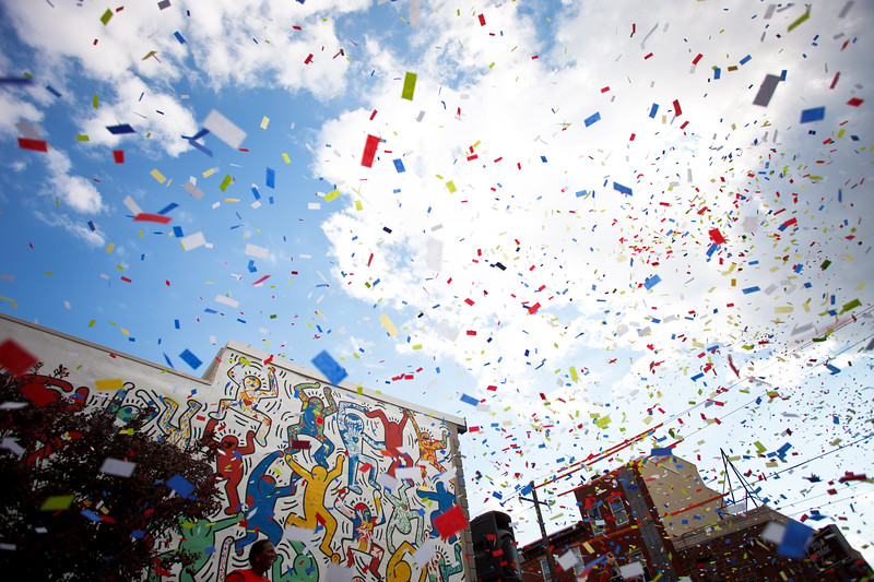 Confetti flies at at the dedication of We The Youth, Keith Haring's freshly restored mural in South Philadelphia.