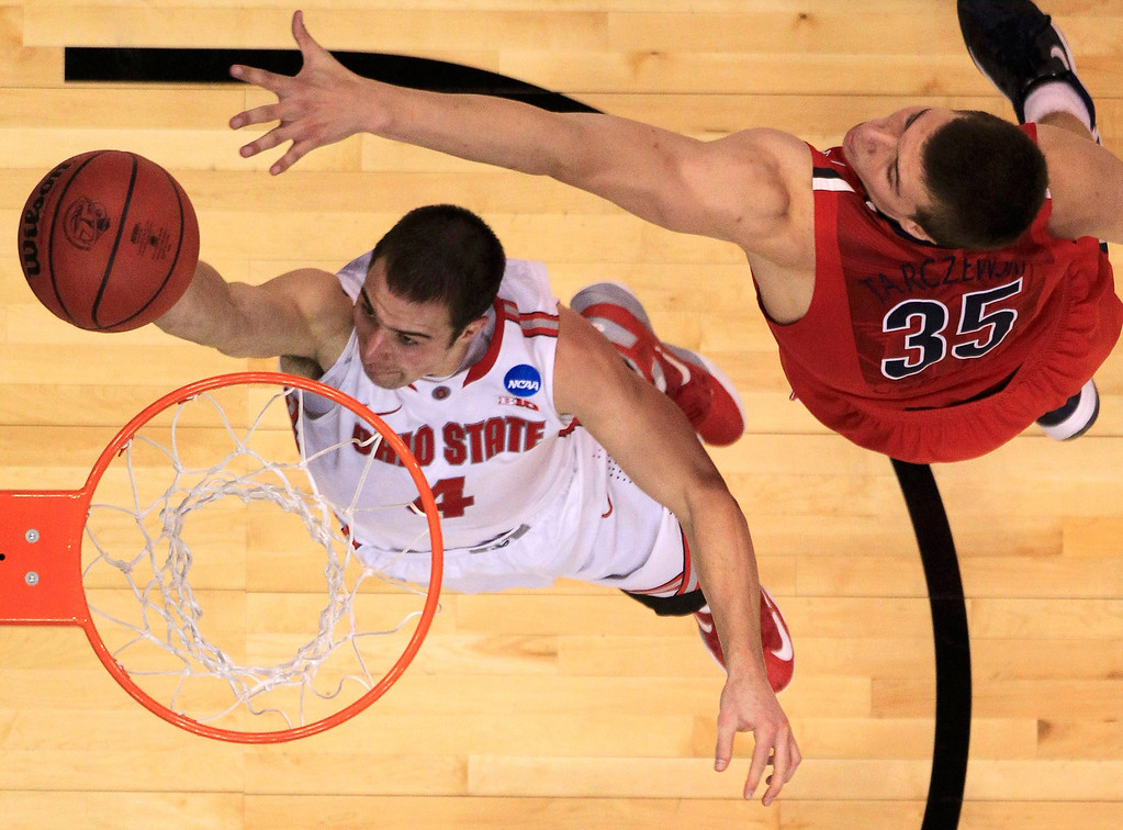 . Ohio State Buckeyes guard Aaron Craft (4) scores on Arizona Wildcats center Kaleb Tarczewski (35) during the second half in their West Regional NCAA men\'s basketball game in Los Angeles, California March 28, 2013. REUTERS/Lucy Nicholson