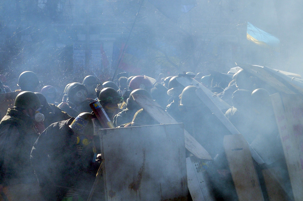 . Anti-government protesters shield themselves during clashes with riot police in front of the Parliament in central Kiev on February 18, 2014.     AFP PHOTO/ SERGEI  SUPINSKY/AFP/Getty Images