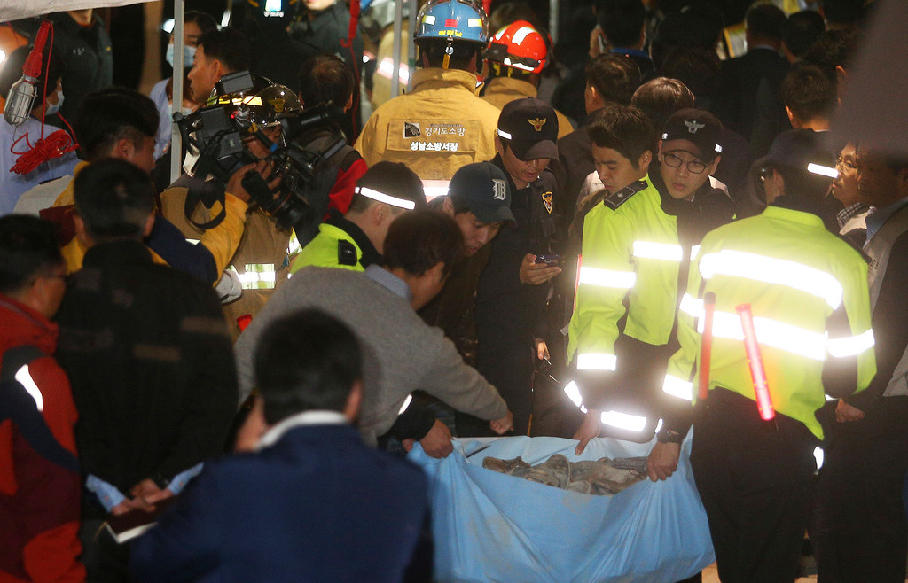 . Police officers carry a sack containing shoes of victims after a ventilation grate was collapsed at an outdoor theater in Seongnam, south of Seoul, South Korea, Friday, Oct. 17, 2014. (AP Photo/Yonhap, Shin Young-geun)