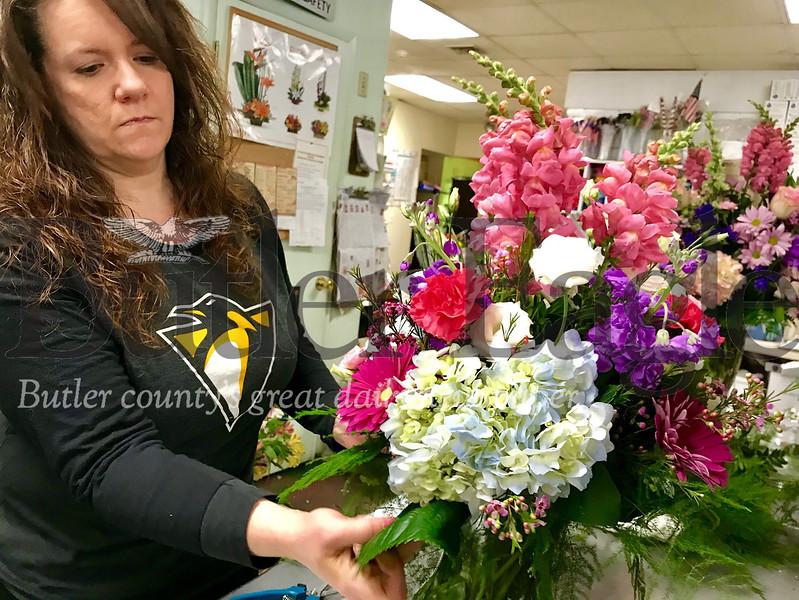 Michele Craig, a floral designer at Bortmas, the Butler Florist, sets filler into a Valentine's Day floral arrangement
